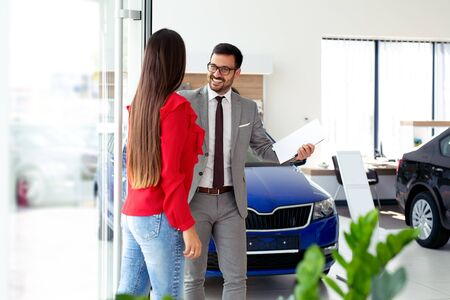 Happy girl enjoys buying a new car in the showroom