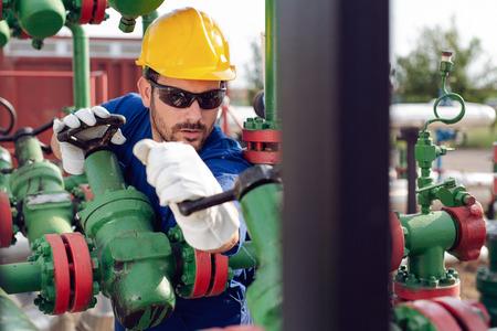 Travailleur du pétrole tournant la vanne sur la plate-forme pétrolière