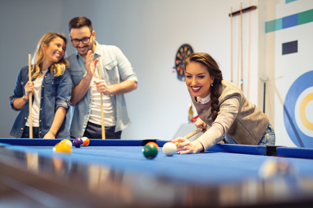 Coworkers playing a game pool after a long work day.