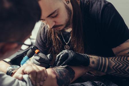 Professional tattoo artist makes a tattoo on a man's hand Stock fotó