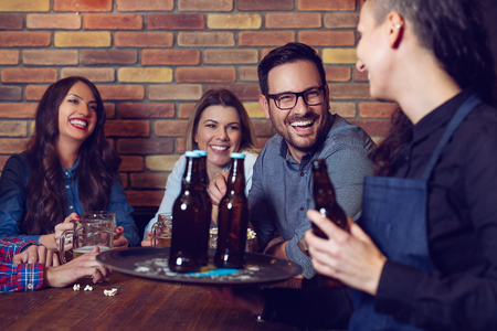 Cheerful group of friends joking and laughing with a waiter in pub. Stock Photo