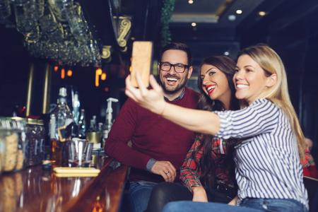 Drei Freunde machen Selfie in einer Bar.