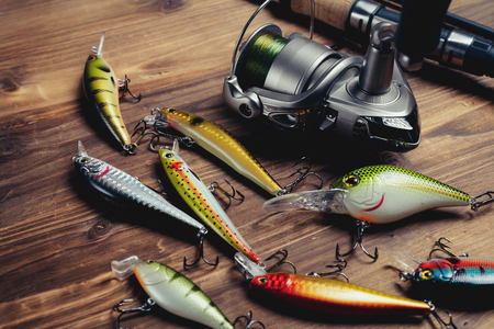Fishing tackle - fishing spinning, hooks and lures on wooden background Stock Photo