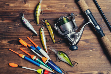 Fishing tackle - fishing spinning, hooks and lures on wooden background 写真素材