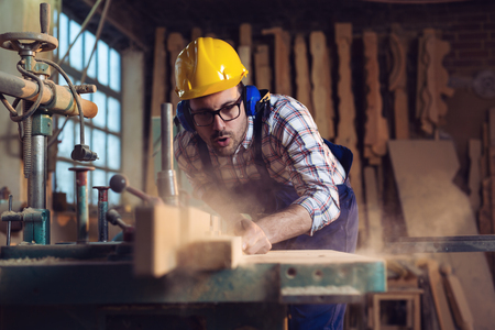 Carpenter cutting a piece of wood in his woodwork workshop Imagens