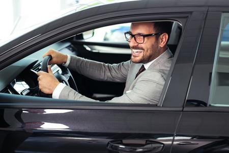 El empresario está sentado en el coche en la sala de exposiciones