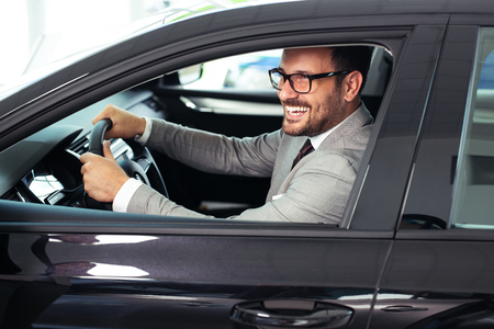 L'uomo d'affari è seduto in macchina nello showroom