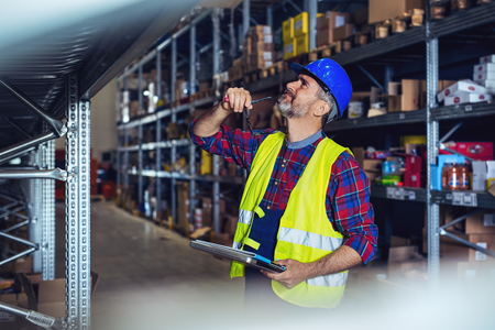 Warehouse worker hand holding clipboard with load control the shipment into a truck Standard-Bild