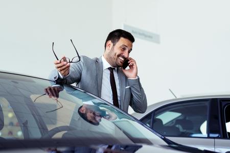 Biznesmen rozmawia przez telefon w salonie samochodowym