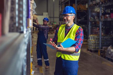 Gestionnaire d'entrepôt écrivant sur le presse-papiers dans un grand entrepôt