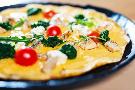 Omelette in a plate on wooden table Imagens