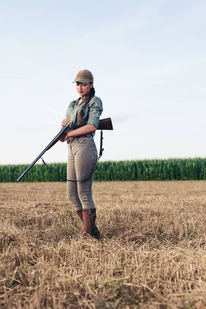 Attractive female hunter reloading her rifle.