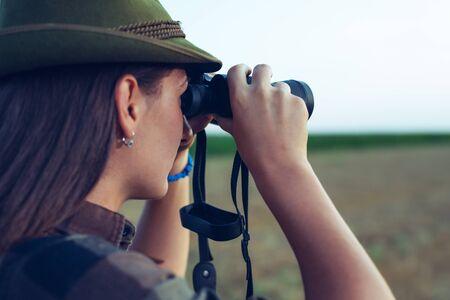 Hunter Looking Over The Field Through Binoculars