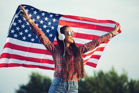 Junges Mädchen mit Sonnenbrille und amerikanischer Flagge, Musik genießen Standard-Bild