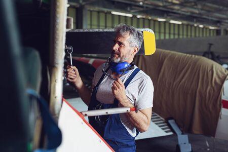 Mechanic near airplanes engine. Male Aero Engineer Working On airplanes In Hangar.