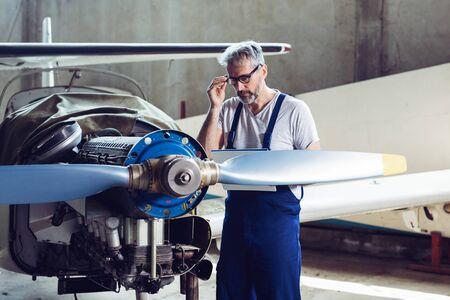 Aircraft maintenance mechanic inspects plane engine 版權商用圖片