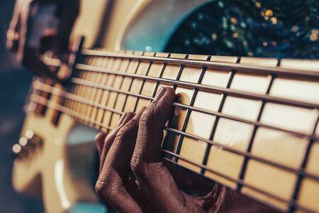 Closeup photo of bass guitar player hands
