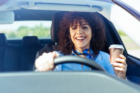 Businesswoman drinking coffee while driving car.