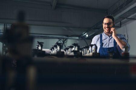 Industrial man engineer using smartphone.