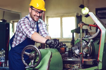 Turner worker is working on a lathe machine in a factory. Foto de archivo