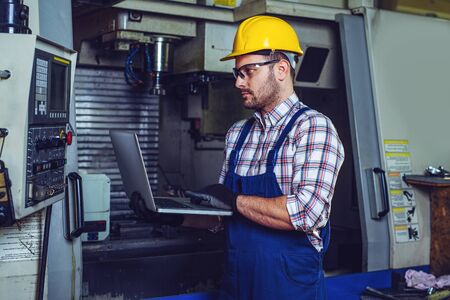 Engineer Operating CNC Machinery In Factory