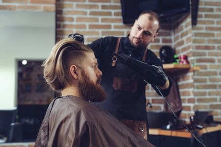 Barber drying male hair in hairdressing salon. Archivio Fotografico