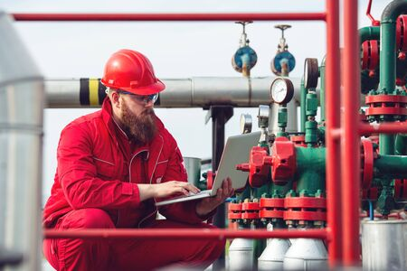 Engineer wearing safety helmet using laptop with oil refinery industry plant background.
