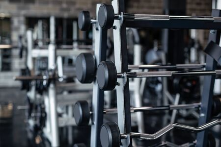 Sports equipment in gym. Barbells of different weight on rack.