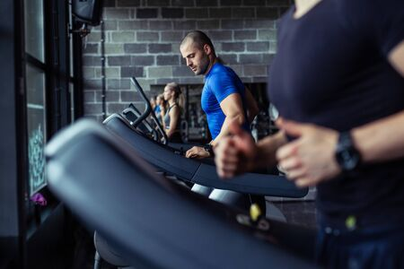 Young man in sportswear running on treadmill at gym.
