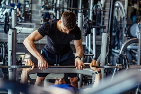 Muscular young man is exercising in the gym with his personal fitness instructor.