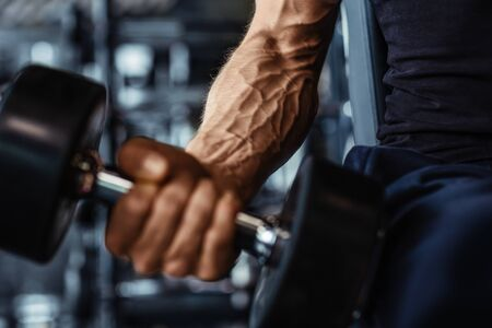 Hand holding dumbbell.Close up.Muscular arm in the gym.