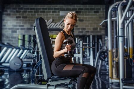 Strong woman working out with dumbbells.