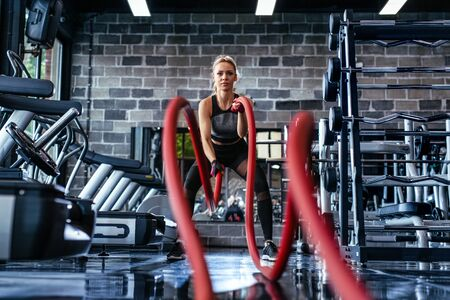 Battle ropes session. Attractive young fit and toned sportswoman training in gym.