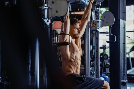 Young bodybuilder training in the gym. Handsome man at the gym doing exercises.