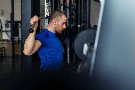 Fit man exercising at the gym on a machine.
