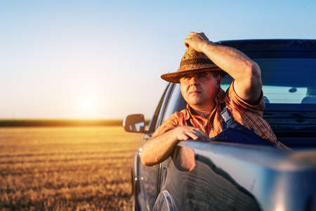 Young man in straw hat driving truck. Life on a farm. Standard-Bild