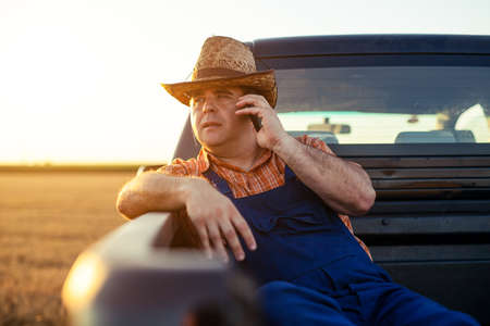Farmer talking on smart phone. Standard-Bild - 154197112