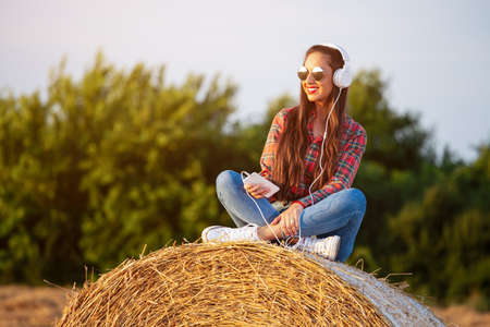 Beautiful girl sitting on a haystack, listening to music , enjoying sunset. Standard-Bild - 154931822