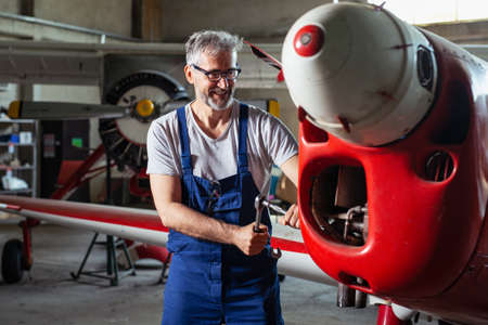 Senior engineer repairing aircraft engine