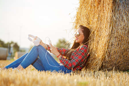 Girl sitting in the wheat field with her headset on. She is leaning her back on a haystack. Foto de archivo