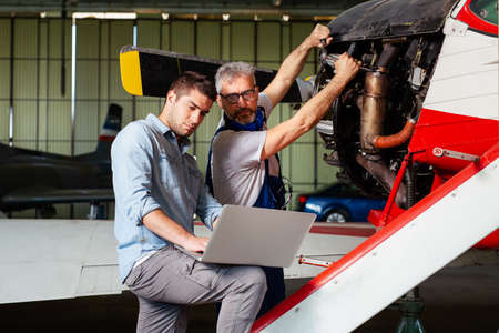 Engineer looking at laptop for maintenance an airplane. Standard-Bild - 154931830