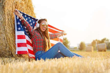 Young woman with an American flag on the wheat field. Standard-Bild - 154931832