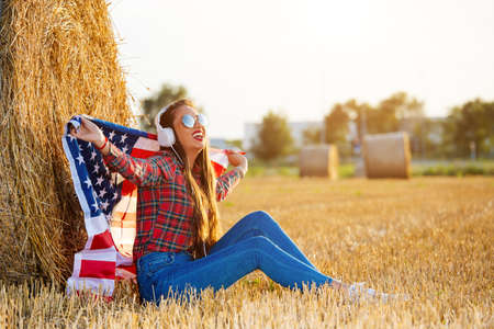 Young woman with an American flag on the wheat field.