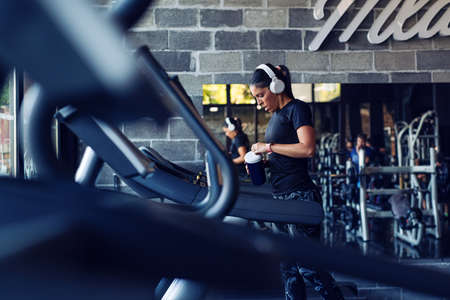 Fit young woman resting after workout or exercise in fitness gym Standard-Bild