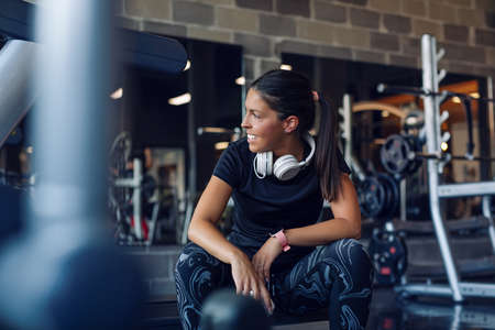 Fit young woman resting after workout or exercise in fitness gym. Standard-Bild