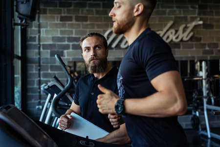 Personal training with a trainer on a treadmill. Standard-Bild