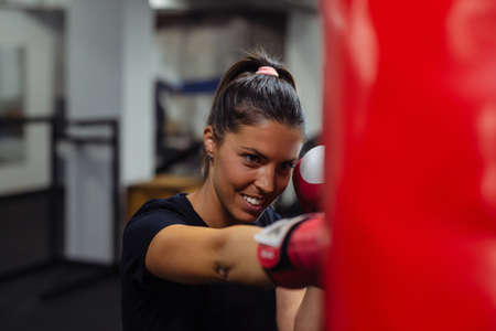 Young woman doing boxing training at the gym. Standard-Bild - 155382970