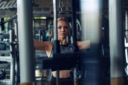 Young fitness woman execute exercise with exercise-machine in gym. Stockfoto