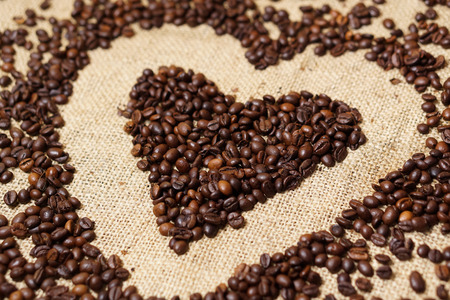 Love heart made of coffee beans on sackcloth