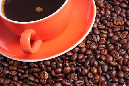Coffee in orange cup surrounded with coffee beans